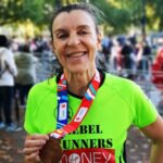 Carina at the London Marathon, smiling and holding her medal